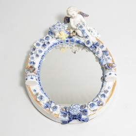 A mirror with blue and white ceramic frame